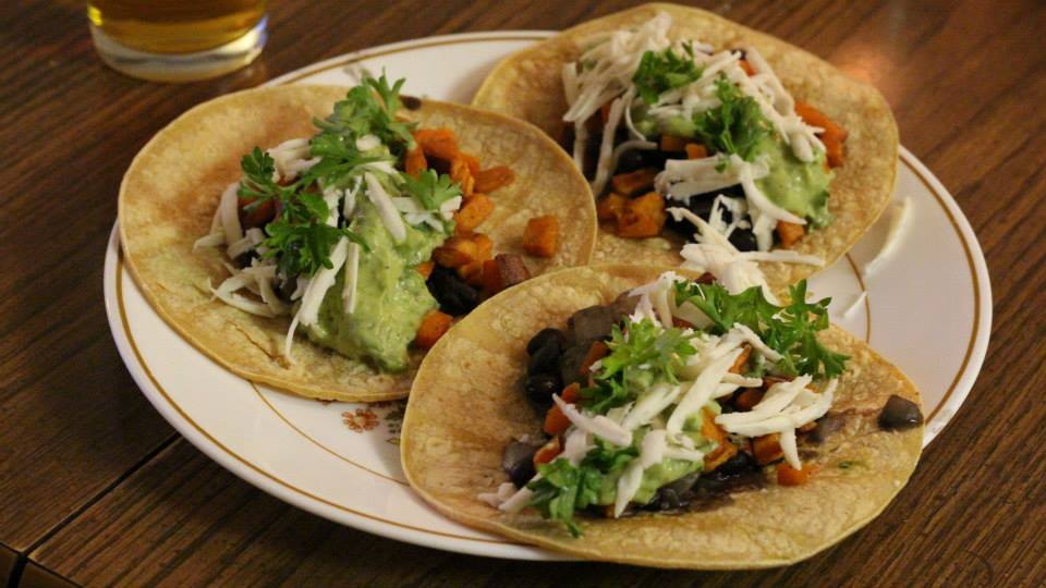 spicy vegan black-bean sweet potato tacos with an avocado-lime-cilantro sauce.